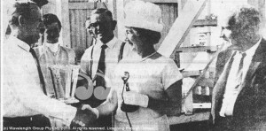 Scone owner, Harry Hayes (left) receives his winner's trophy from Mrs. Quinn at an Aberdeen meeting in the 1960s, watched by former trainer Eric Cribb and then Aberdeen Race Club President Mr. Arthur Taylor (right).
