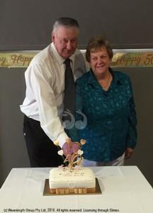 Errol and Beryl Bates cutting their 50th wedding anniversary cake.
