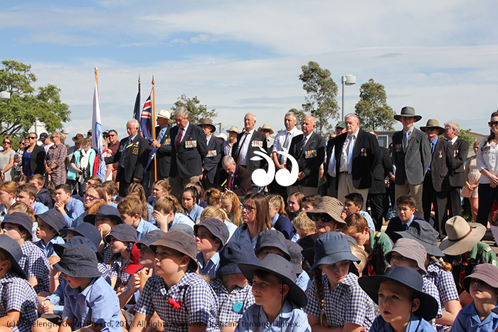 Local school children turn out in strong numbers to honour the ANZAC's, with returned soldiers standing behind them.