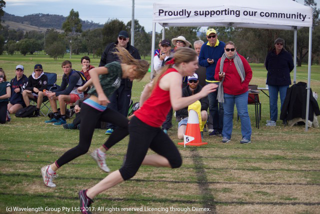 Mersadies Cadalbert crossing the finish line to claim Queen of the Track at the St Joseph's athletics carnival, with Tyler Brown close behind.