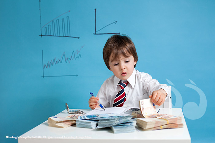 Young boy, counting money and taking notes. Adobe Stock Photo